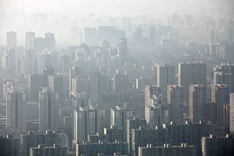 Smog fills the morning air above housing block towers in Bejing.