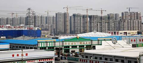 Construction cranes build a housing block in the outskirts of Beijing.