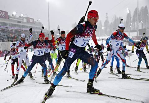 """The picture I was hoping for worked out well to get the big group of athletes taking off from the start together. With a 50mm lens they came right toward us with the biathlon stadium behind them. A few minutes early or later and the scene would have looked completely different thanks to the changing weather."" Anton Shipulin (13), of Russian, takes off for the men's 15K mass start biathlon"