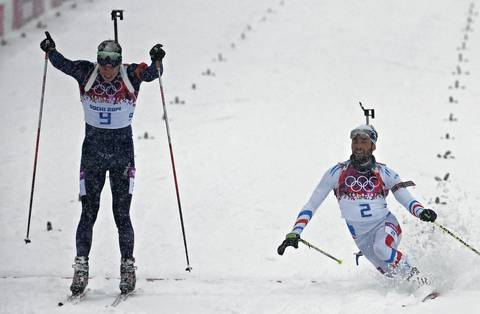 """I moved to the finish (climbing up and down scaffolding into a tower) and made some overalls of the race from there. The race was very close with Norwegian Emil Hegle Svendsen barely holding off a diving and favored Martin Fourcade at the finish line. It was easy to see just how exhausted the competitors were after a 40 minute race in conditions like that."" Emil Hegle Svendsen, left, of Norway, celebrates winning the gold medal ahead of Martin Fourcade, of France."
