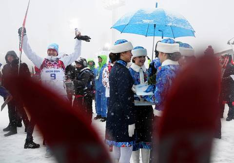 """Afterward I spotted a feature of the women who are part of the flower ceremony standing under a snow-covered umbrella. As I framed them between some skis, gold medalist Svedsen popped in and continued his celebration."""