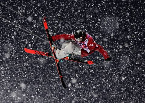 """The snow continued to waver in intensity and during the heaviest snowfall the telephoto pictures had great impact under the flood lights."" Matt Margetts, of Canada, competes in qualifying for the men's ski halfpipe."