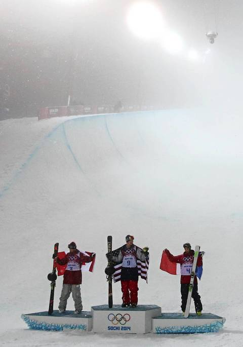 """Wise's first run was good enough for the gold and he celebrated at the bottom. By the time they did the flower ceremony the winners were in front of a halfpipe that just disappeared into the fog."" Silver medalist Mike Riddle, left, of Canada, gold medalist David Wise, center, of the USA, and bronze medalist Kevin Rolland, right, of France, celebrate their victories."