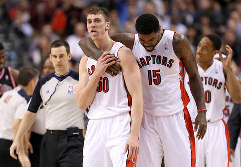 The Raptors' forward Tyler Hansbrough is restrained by Amir Johnson after receiving a foul.