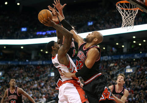 The Raptors' Amir Johnson shoots while defended by Taj Gibson.
