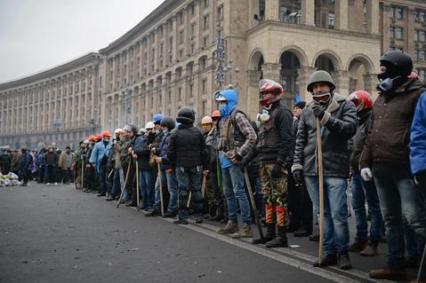 Anti-government protesters prepare to push forward during continued clashes with police in Independence square, despite a truce agreed between the Ukrainian president and opposition leaders in Kiev, Ukraine.