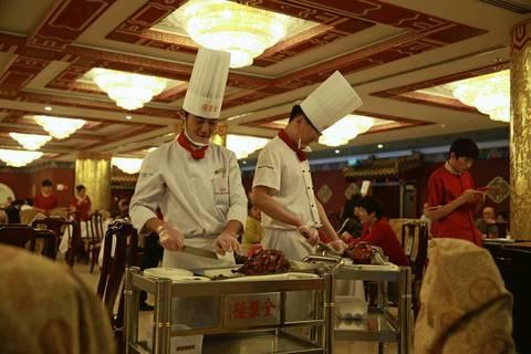 Chefs slice Peking Duck at a restaurant off Wangfujing Street in Beijing.
