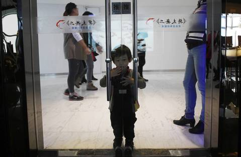 A boy gazes at a goldfish tank while standing behind a glass door entrance to a sushi restaurant.