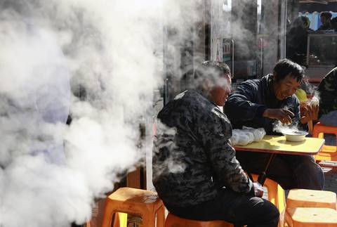 Workers take their lunch breaks at a restaurant across the street from the Oriental Fisherman's Wharf complex in Shanghai.
