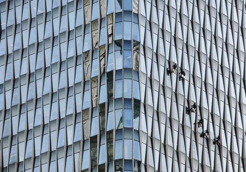 Window washers descend the exterior of the 38-floor Taiping Financial Tower in the Pudong district of Shanghai.
