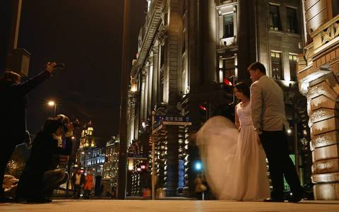 A bride and groom pose for portraits on The Bund waterfront area of Shanghai.
