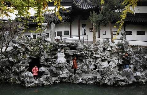 Tourists walk through rock formations in the Lion Forest Garden in Suzhou.