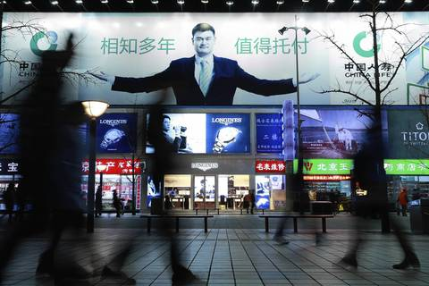 An advertisement with former NBA basketball player Yao Ming greets pedestrians on Wangfujing Street in Beijing.