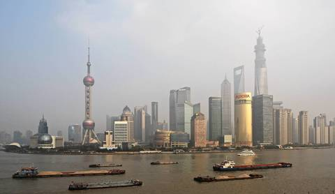 Barges move along the Huangpu River in Shanghai. The city's Pudong district boasts the world's only trio of supertall skyscrapers: the Jin Mao Tower, the Shanghai World Financial Center and the Shanghai Tower.