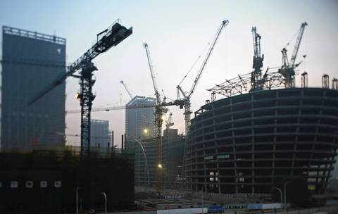 Construction cranes dot the skyline of the Binhai New Area development in Tianjin.