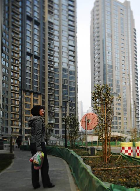 A resident walks through the courtyard of the Heping Residential Development, designed by Ralph Johnson of Perkins+Will, in Tianjin. The project proved an aesthetic and financial disappointment for the architects as cost-cutting by developers, who ultimately went bankrupt, dulled the visual impact of the complex.