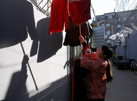 "Fan Xinghua, 35, retrieves laundry hanging on a clothesline in the Paoju Hutong in Beijing. ""Everyone knows each other here,"" she said. ""That's good for the children. They have lots of others to play with."""