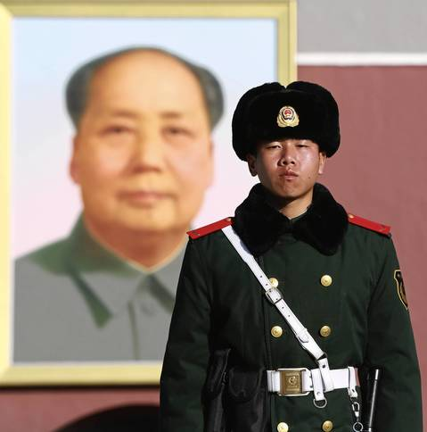 A soldier guards the entry gate adorned with a portrait of Mao Zedong at Tiananmen Square in Beijing.
