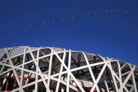Kites fly next to Beijing National Stadium, also known as the Bird's Nest, during a clear day in Beijing.