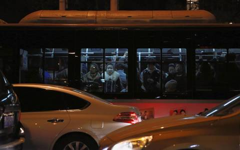 Commuters are packed on a bus in Beijing. In some urban areas, the streets are clogged with cars and the air choked with pollution.