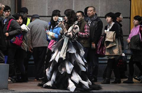 A woman in costume on Zhongshon East 1st Road, also known as The Bund.