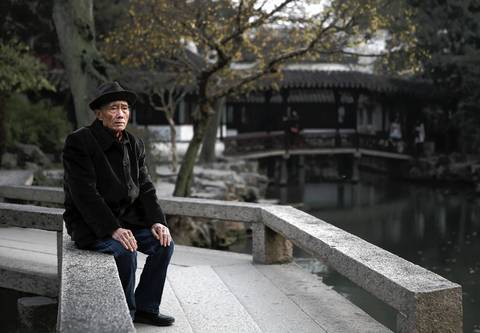 A man spends a quiet moment in The Humble Administrator's Garden in Suzhou.