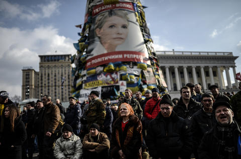 Anti-government protesters stand beneath a giant poster of jailed former Ukrainian Prime minister Yulia Tymoshenko as they attend a rally on Independence square in Kiev.