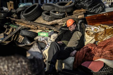 An anti-government protester sleeps behind a barricade on Kiev's Independentce square.