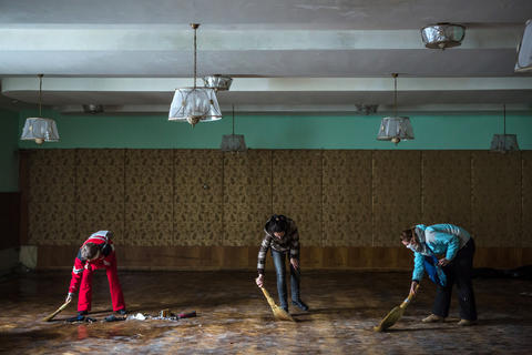 Women clean inside the partially burned Trade Unions Building, which has served as a de facto headquarters for anti-government protesters on Independence Square.