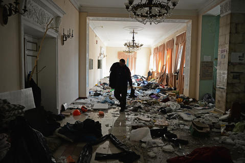 People search through debris inside the International Centre of Culture and Arts as Anti- Government demonstrators continue to occupy Independence Square.