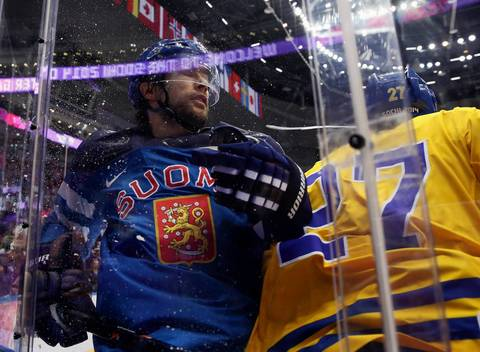 """Along the glass you get to see the players slam right above you and shake the boards. Finland's Tuomo Ruutu, left, took a hit with a spray of ice behind him."""