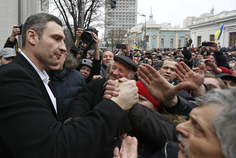 Ukrainian opposition leader and head of the UDAR (Punch) party and former boxer Vitaly Klitschko (L) greets a supporter as he meets with anti-government protesters outside the Ukrainian Parliament building in Kiev.