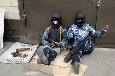 A member of Berkut anti-riot unit makes victory sign as troops prepare to leave their barracks in Kiev.