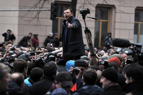 An opposition party member addresses the crowd outside the Parliament in Kiev.