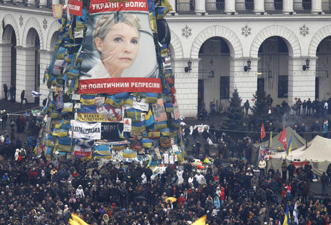 Anti-government protesters stand front of a poster showing then jailed Ukrainian opposition leader Yulia Tymoshenko in the Independence Square in Kiev.