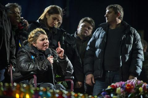 Ukrainian opposition leader Yulia Tymoshenko (L, in wheelchair) is watched by her her daughter Yevgenia (2-L, standing) and other unidentified supporters as she speaks to a crowd at a rally in Kiev Ukraine.