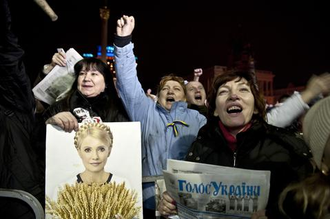 An opposition protester holds a picture of newly freed Ukrainian opposition icon Yulia Tymoshenko as she delivers a speech during a rally at Independence Square in Kiev.