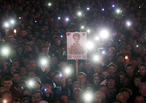 Anti-government protesters hold a portrait of Ukrainian opposition leader Yulia Tymoshenko while she speaks to a crowd at a rally in Kiev Ukraine on Feb. 22.