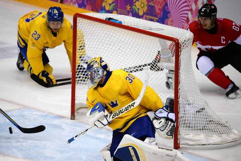Canada forward Sidney Crosby (87) eyes a chance as Sweden goalie Henrik Lundqvist (30) keeps the puck out of the net in the first period of the gold medal men's hockey game at the Winter Olympics in Sochi, Russia.