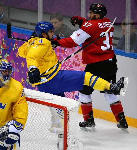 Canada forward Patrice Bergeron (37) hits Sweden defenseman Niklas Hjalmarsson (4) in the first period of the gold medal men's hockey game at the Winter Olympics in Sochi, Russia.