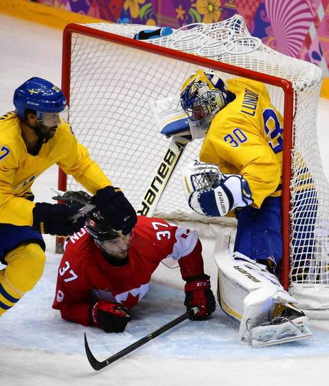Canada forward Patrice Bergeron (37) slides into Sweden goalie Henrik Lundqvist's net in the first period of the gold medal men's hockey game at the Winter Olympics in Sochi, Russia.