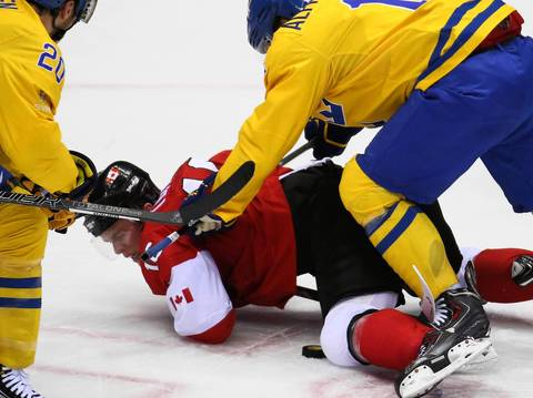 Canada forward Jonathan Toews (16) takes a hit from Sweden forward Daniel Alfredsson (11) in the first period of the gold medal men's hockey game at the Winter Olympics in Sochi, Russia.