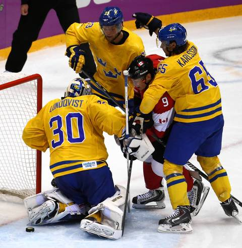 The puck gets behind Sweden goalie Henrik Lundqvist (30) but Canada forward Matt Duchene (9) can't score in the second period of the gold medal men's hockey game at the Winter Olympics in Sochi, Russia