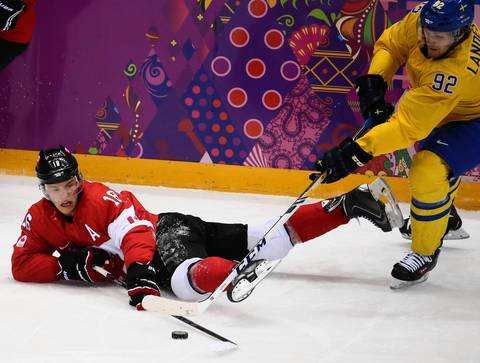 Canada forward Jonathan Toews (16) moves the puck against Sweden forward Gabriel Landeskog (92) in the second period of the gold medal men's hockey game at the Winter Olympics in Sochi, Russia.