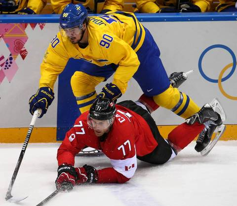 Sweden forward Marcus Johansson (90) hits Canada forward Jeff Carter (77) in the first period of the gold medal men's hockey game at the Winter Olympics in Sochi, Russia.