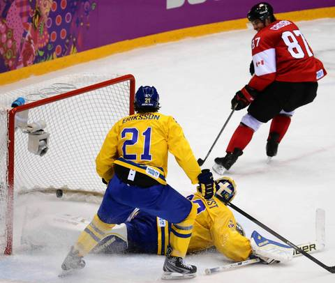 Canada forward Sidney Crosby (87) scores against Sweden goalie Henrik Lundqvist (30) in the second period of the gold medal men's hockey game at the Winter Olympics in Sochi, Russia.
