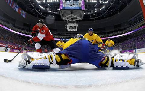 Canada's Sidney Crosby (87) scores on a breakaway past Sweden's goalie Henrik Lundqvist during the second period of their men's ice hockey gold medal game at the Sochi 2014 Winter Olympic Games