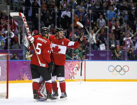 Canada's goalie Carey Price (obscured ) and teammates Dan Hamhuis and Jonathan Toews (R) celebrate after defeating Sweden in the men's ice hockey gold medal game at the 2014 Sochi Winter Olympic Games