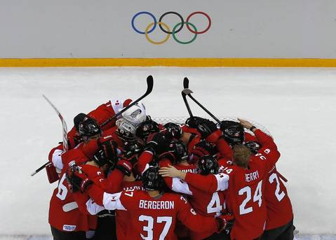 Canada's players huddle as they celebrate defeating Sweden in their men's ice hockey gold medal game at the Sochi 2014 Winter Olympic Games.