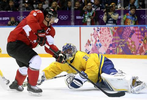 Sidney Crosby (L) of Canada scores against Henrik Lundqvist (bottom) goalkeeper of Sweden during the Men's Gold Medal match between Sweden and Canada at the Bolshoy Ice Dome.